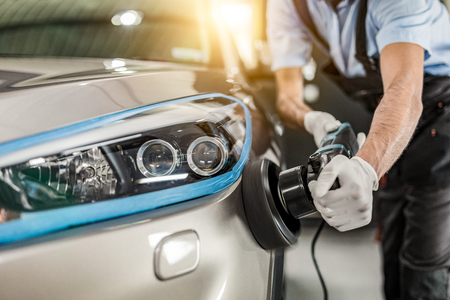 Détail de la voiture - L'homme tient un polisseur dans la main et polit la voiture. Mise au point sélective.