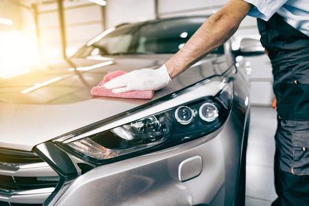 Auto Detaillierung - Der Mann hält die Mikrofaser in der Hand und poliert das Auto . Selektiver Fokus Standard-Bild - 82172145