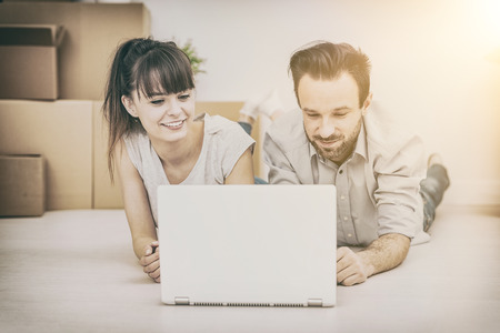 Un jeune couple assis dans un nouvel appartement et utilise un ordinateur portable. Discuter des projets de réparation à domicile tout en se déplaçant. Banque d'images