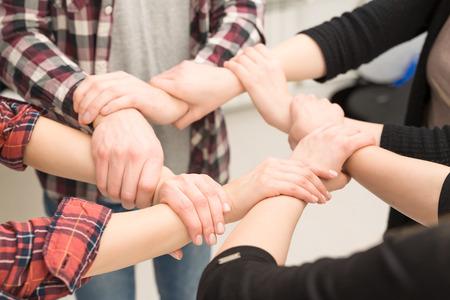Un groupe de jeunes accueille fort. Signe de confiance et de travail d'équipe. Banque d'images
