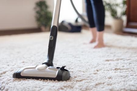 집에서 카펫 청소하는 동안 진공 청소기를 사용하는 젊은 여자.