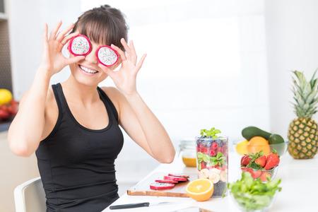 Une jeune femme heureuse met des tranches de fruits de dragon comme des lunettes. Manger sainement - concept. Banque d'images