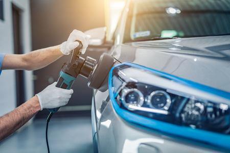詳しく述べる車 - 男の手にポリッシャーを保持し、車を磨きます。選択と集中。