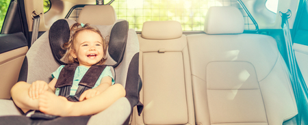Beautyful smiling baby girl fastened with security belt in safety car seat