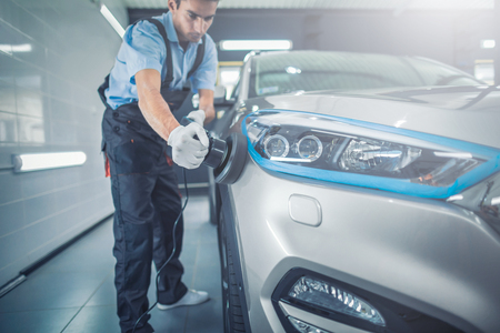 Car detailing - Man holds a polisher in the hand and polishes the car. Selective focus. Banque d'images