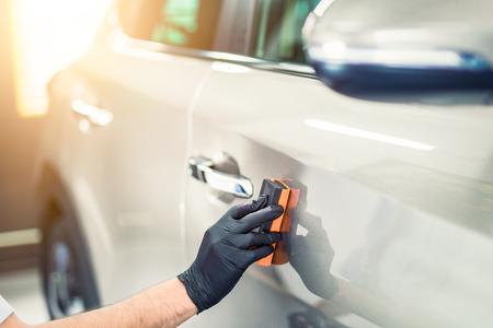 자동차 자세히 설명 - 남자는 자동차에 나노 보호 코팅을 적용합니다. 선택적 포커스입니다. 스톡 콘텐츠