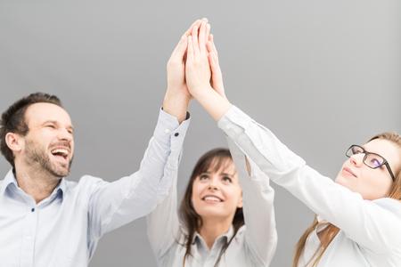 Groupe de gens d'affaires qui apprécient et célèbrent le succès du travail en équipe. Ils forment des mains vers le haut dans un geste de victoire. photo