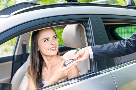 A young beautiful woman receive the keys to the new car from the dealer.