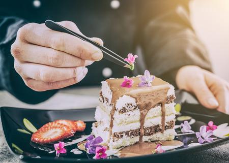 Chef-kok chocolade gebak dessert bloem plaat fijne garnering ijs maken cake koken eten perfect eten toevoegen gebouw concept - stock afbeelding Stockfoto