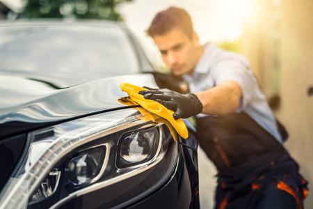 Car detailing - mężczyzna trzyma w ręku mikrofibrę i poleruje auto. Selektywna ostrość. Zdjęcie Seryjne