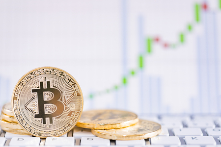Bitcoin gold coin and defocused chart background. Virtual cryptocurrency concept.