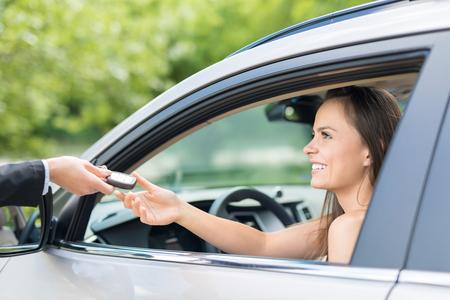 Eine junge schöne Frau erhält die Schlüssel zum neuen Auto vom Händler. Standard-Bild - 82771145