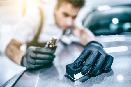 Car detailing - Man applies nano protective coating to the car. Selective focus. Foto de archivo