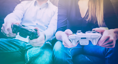 gaming game play fun gamer gamepad guy pad player girl controller online video closeup sitting focus console person concept - stock image Stock Photo - 83536869