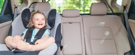 Beautyful niña sonriente sujetó con cinturón de seguridad en asiento de seguridad de coche Foto de archivo - 83536636