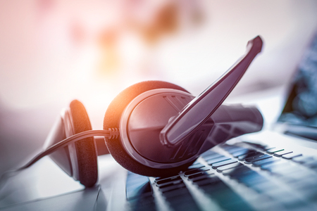 Soporte de comunicación, centro de llamadas y atención al cliente. Auriculares VOIP en el teclado de la computadora portátil.