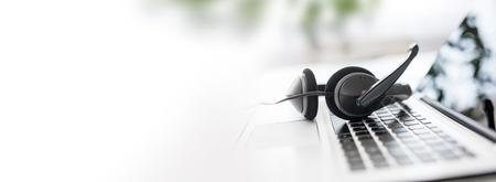 Soporte de comunicación, centro de llamadas y atención al cliente. Auriculares VOIP en el teclado de la computadora portátil. Foto de archivo