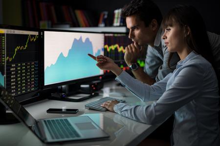 Analyser les données, les graphiques et les rapports à des fins d'investissement. Les commerçants créatifs d'équipe. photo