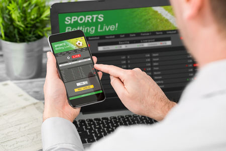 betting bet sport phone gamble laptop over shoulder soccer live home website concept - stock image Фото со стока - 83536601