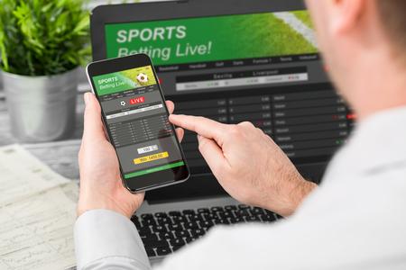 Wedden wedden sport telefoon gok laptop over schouder voetbal live home website concept - stock afbeelding