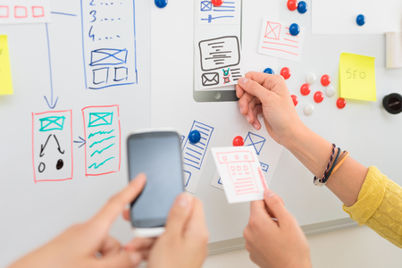 A group of people designers designing a wireframe application of mobile phone and responsive websites. Teamwork and user experience. 스톡 콘텐츠