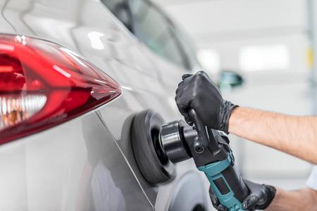 Car detailing - De man houdt een polishager in de hand en poets de auto. Selectieve focus.