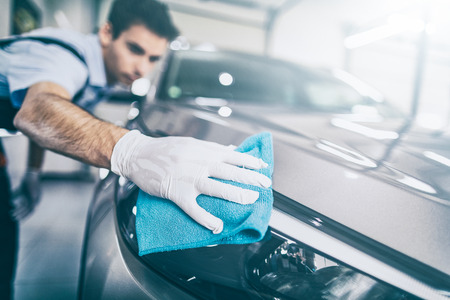 Détail de la voiture - l'homme tient la microfibre à la main et polit la voiture. Mise au point sélective. photo