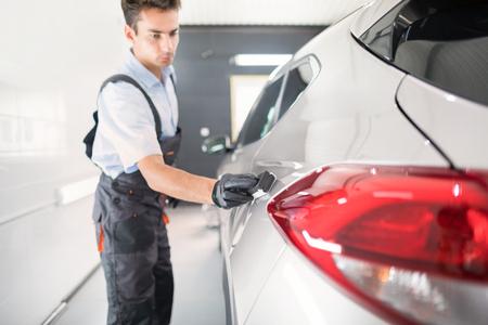 Détail de la voiture - Man applique un revêtement protecteur nano à la voiture. Mise au point sélective. photo