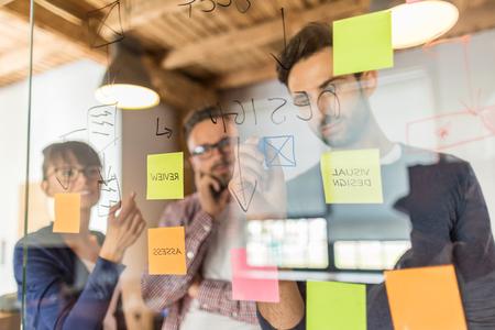 Les gens d'affaires se rencontrent au bureau et utilisent des notes pour partager l'idée. Concept de remue-méninges. Note collante sur la paroi en verre. Banque d'images - 84339702