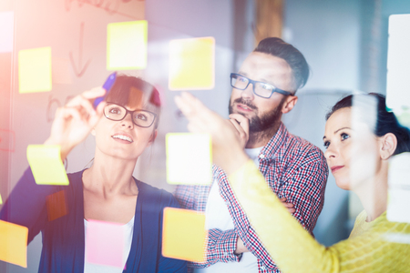 Business people meeting at office and use sticky notes to share idea. Brainstorming concept. Sticky note on glass wall. Stock Photo