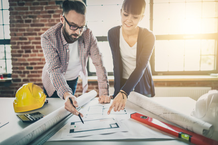 Architects working with blueprints in the office. Teamwork architects concept. Stock Photo