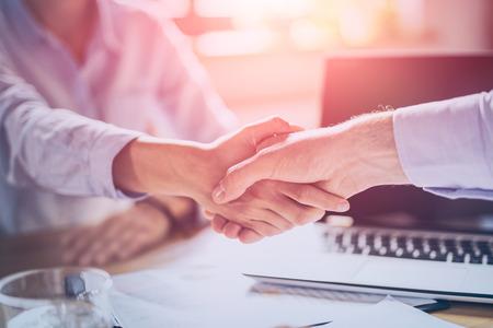 Gente de negocios dándose la mano, terminando la reunión. Empresarios exitosos apretón de manos después de buen trato.