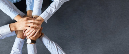 Close up vista superior de jóvenes empresarios poniendo sus manos juntas. Pila de manos. Concepto de unidad y trabajo en equipo.