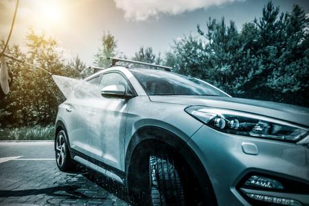 Handmatige auto wassen met onder druk water in de car wash buiten. Stockfoto