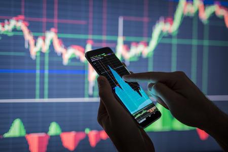 Homme d'affaires vérifiant les données boursières. Il utilise un téléphone mobile. Analyse des données économiques sur le forex gagnent un graphique. Banque d'images