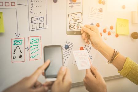 Un groupe de designers personnes qui conçoivent une application filaire du téléphone mobile et des sites Web adaptés. Travail d'équipe et l'expérience utilisateur.