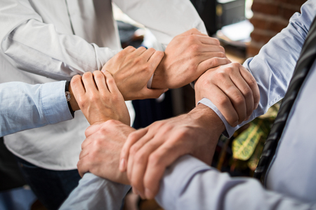 一緒に彼らの手を置く若いビジネス人のトップのビューを閉じます。手のスタック。団結とチームワークの概念。