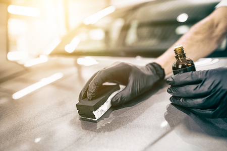Dettaglio dell'automobile - L'uomo applica rivestimento protettivo nano all'auto. Messa a fuoco selettiva. Archivio Fotografico - 84412916