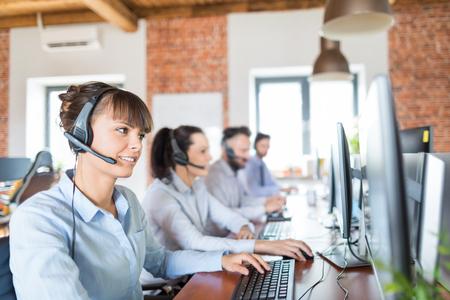 Travailleur du centre d'appel accompagné de son équipe. Opérateur de soutien clientèle souriant au travail. Jeune employé travaillant avec un casque.