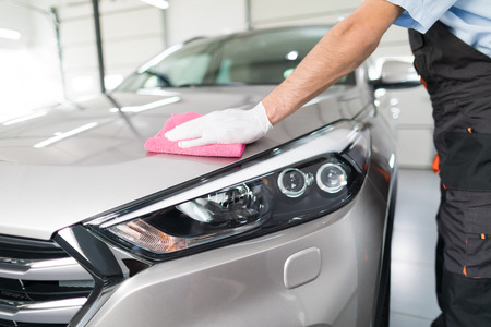 Auto-Detaillierung - der Mann hält die Mikrofaser in der Hand und poliert das Auto. Selektiver Fokus Standard-Bild - 84412922