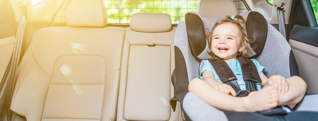 Schönes lächelndes Baby, das mit Sicherheitsgurt im Sicherheits-Autositz befestigt ist Standard-Bild - 84412924
