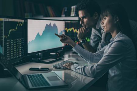 Analyser les données, les graphiques et les rapports à des fins d'investissement. Les commerçants créatifs d'équipe. Banque d'images