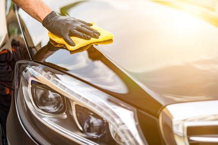 Détail de la voiture - l'homme tient la microfibre à la main et polit la voiture. Mise au point sélective.