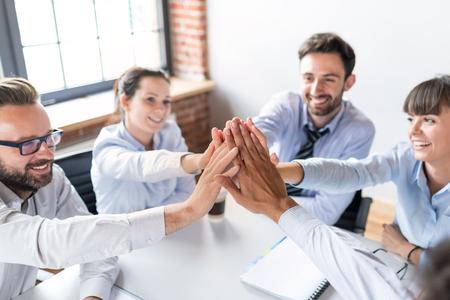 Les gens d'affaires heureux montrent le travail en équipe et donnent cinq au pouvoir. Concepts du travail d'équipe.