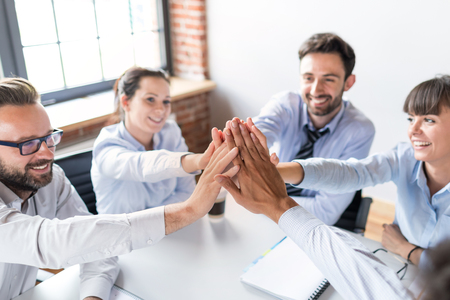 Business people happy showing team work and giving five in office. Teamwork concepts. Foto de archivo