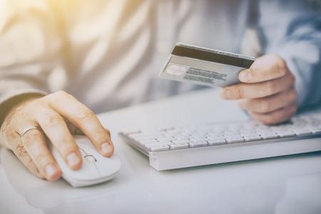 Mains tenant une carte de crédit et utilisant un ordinateur. Les concepts de paiement et de vente en ligne.