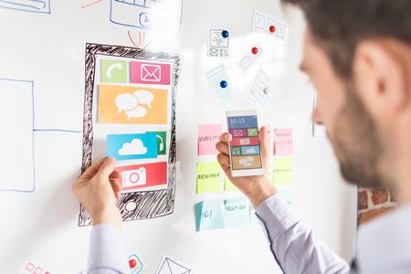 Hombre del diseñador que dibuja el desarrollo de la aplicación del sitio web ux y que sostiene el teléfono inteligente en la mano. Concepto de experiencia del usuario. Foto de archivo