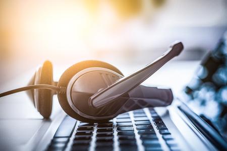 Support de communication, centre d'appels et service d'assistance client. Casque VOIP sur le clavier de l'ordinateur portable. Banque d'images