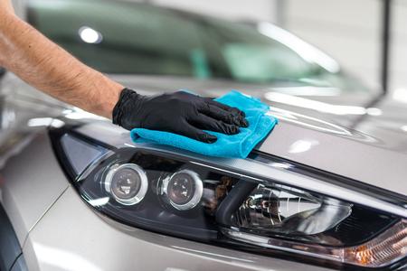 Détail de la voiture - l'homme tient la microfibre à la main et polit la voiture. Mise au point sélective. Banque d'images