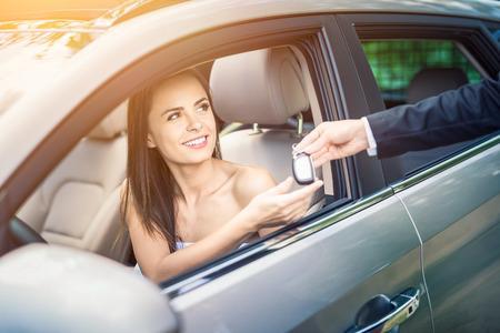 Een jonge mooie vrouw ontvangt de sleutels van de nieuwe auto van de dealer. Stockfoto